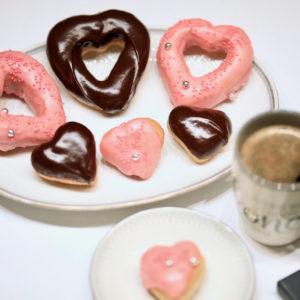 Server hjerteformede donuts med en kopp kaffe